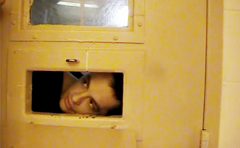 Paul Schlosser peers out the food tray slot in his cell door June 10, 2012. Schlosser, who had injured himself, took the dressing off his wound and was put under observation and videotaped through this food tray slot.