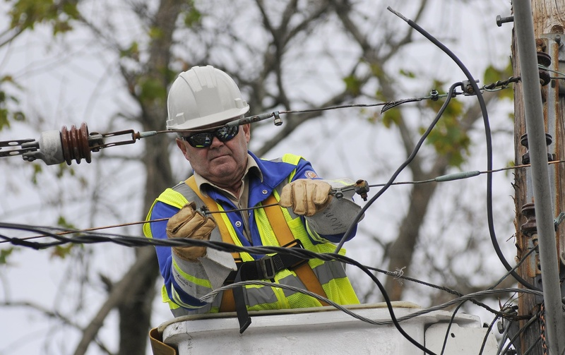 Guy Munn of O'Donnell Line & Electric in Canand works on a power line to restore power on Dyer Street in Saco after a storm.