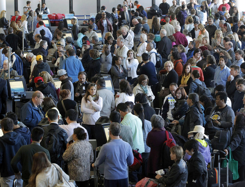 Passengers gather at the American Airlines check-in for flights at Los Angeles International Airport on Tuesday. Computer problems forced American Airlines to ground flights across the country after the airline was unable to check in and book passengers.