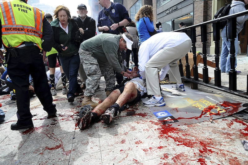 In this April 15, 2013 photo, an injured person is helped on the sidewalk near the Boston Marathon finish line following an explosion in Boston. The bombs that made Boston look like a combat zone have also brought battlefield medicine to their civilian victims. A decade of wars in Iraq and Afghanistan has sharpened skills and scalpels, leading to dramatic advances that are now being used to treat the 13 amputees and nearly a dozen other patients still fighting to keep damaged limbs. (AP Photo/MetroWest Daily News, Ken McGagh, File)