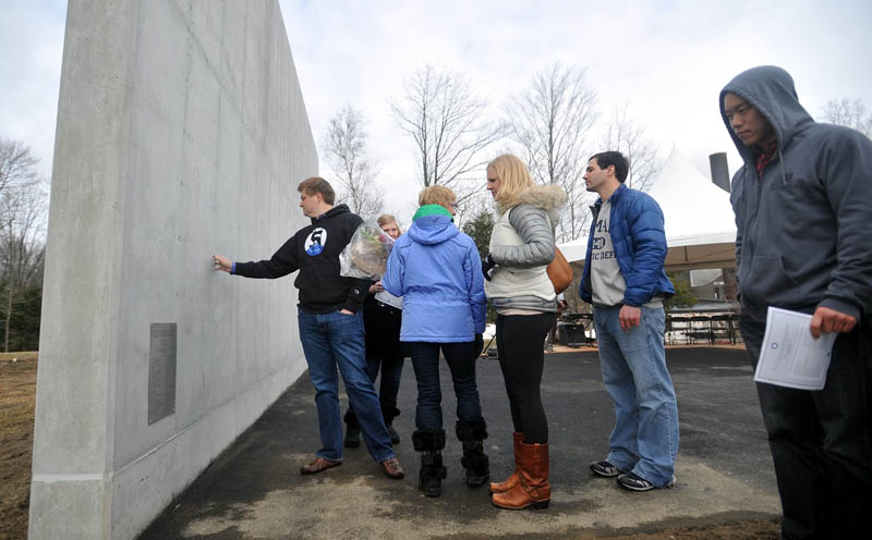 DERRIK'S WALL: Friends and family of Derrik Flahive visit the lacrosse practice wall before the dedication of the Flahive 5 wall at Bill Alfond Field at Colby College on Saturday. The Flahive 5 wall was erected to honor the memory of classmate Derrik Flahive, who drowned while traveling in Chile in 2011.