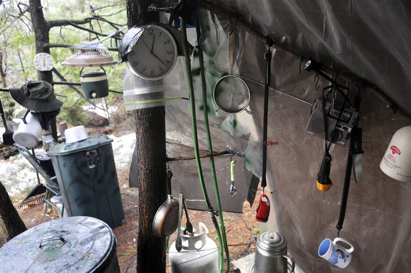 Staff photo by Andy Molloy Coffee cups, lights and a clock hang under a tarp in Christopher Knight's camp Tuesday April 9, 2013 in a remote, wooded section of Rome after police inspected the site where Knight is believed to have lived since the 1990s. Police believe Knight, who went into the woods near Belgrade in 1986, was a hermit who committed hundreds of burglaries to sustain himself. Knight apparently cooked meals with propane he stole, police claim.