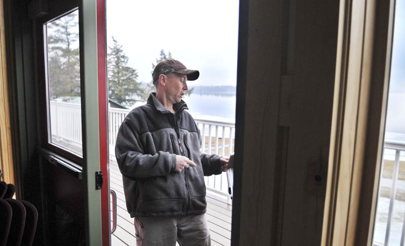 Staff photo by Andy Molloy Pine Tree Camp facility manager Harvey Chesley inspects a door that Christopher Knight alleged broke open in the dining lodge at the Rome camp Tuesday April 9, 2013. Knight, a hermit who lived in the woods since April 1986, was arrested in after breaking into the lodge on April 4, according to Warden Service Sgt. Terry Hughes.