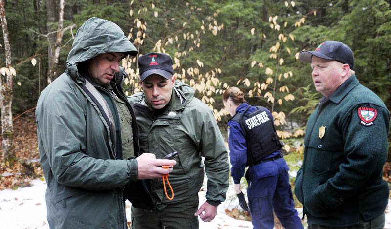 Staff photo by Andy Molloy Game Wardens and State Police get global positioning coordinates before hiking into Christopher Knight's camp in Rome Tuesday April 9, 2013. Police believe Knight, who went into the woods near Belgrade in 1986, was a hermit who committed hundreds of burglaries to sustain himself. His camp is located in a heavily wooded location.