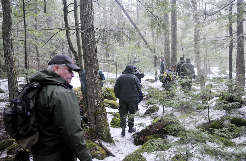 Staff photo by Andy Molloy Game Wardens, State Police and Somerset County Sheriff's deputies hike into Christopher Knight's camp site in Rome Tuesday April 9, 2013. Police believe Knight, who went into the woods near Belgrade in 1986, was a hermit who committed hundreds of burglaries to sustain himself. The camp was located in a heavily wooded location.