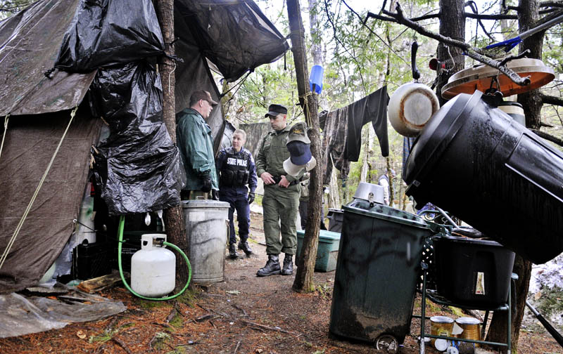 Staff photo by Andy Molloy Game Warden Sgt. Terry Hughes, right, Maine State Police Trooper Diane Vance, center, and Somerset County Deputy Jeremy Leal Tuesday April 9, 2013 inspect Christopher Knight's camp in a remote, wooded section of Rome. Police believe Knight, who went into the woods near Belgrade in 1986, was a hermit who committed hundreds of burglaries to sustain himself.