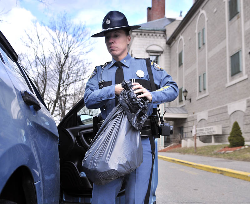 Maine State Police Trooper Diane Perkins-Vance carries a bag of clothing, seized from Christopher Knight, on Sunday at the Kennebec County Correctional Center. Perkins-Vance arrested Knight, who is suspected of committing more than 1,000 burglaries while living in the woods for 27 years, on new charges Sunday, and his bail was increased to $250,000, from $5,000.