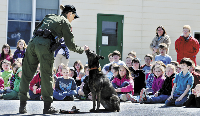 Game Warden Michelle Merrifield and her tracking dog, Duchess, demonstrate how they train together during a visit to the Belgrade Central School on Monday.