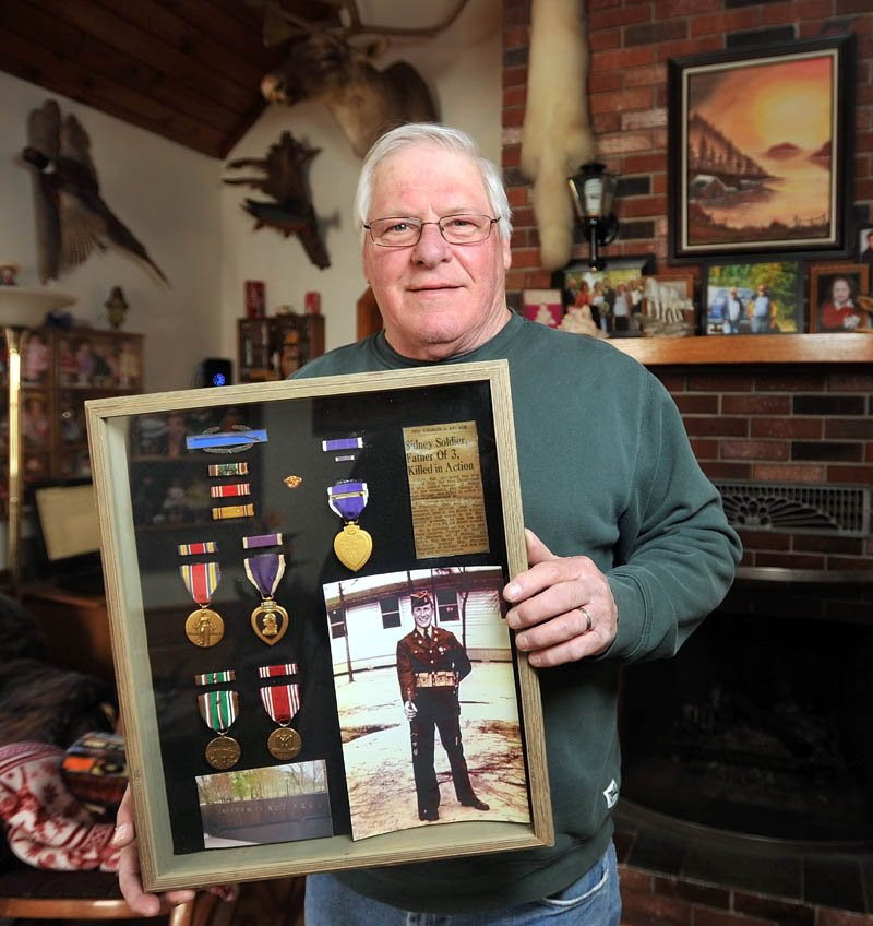 George Savage holds a picture of his father, George, at his Sidney home on Wednesday. Savage's father's remains currently reside in North Cemetery on Madison Avenue in Skowhegan and are in danger of being exposed due to erosion from Whitten Brook.
