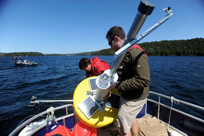 Colby College chemistry professor Whitney King, back center, and Colby College senior Matt LaPine, 22, install a research buoy named Goldie in to Great Pond in Belgrade.