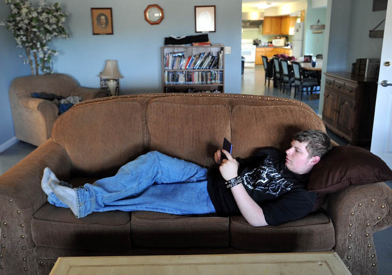 Zach Brady, 17, a junior at Maine Academy of Natural Sciences, lounges on the couch in the common area at the Hall Cottage student dorm on the Goodwil-Hinckley campus in Fairfield on Thursday. The Maine School of Natural Sciences is planning to start a room and board fee for some students that live on campus.