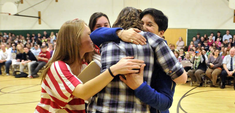 Marisa Weinstein, right, is embraced by former students after Weinstein, music teacher at Warsaw Middle School was presented with the Maine Music Educators Association Educator of the Year award.