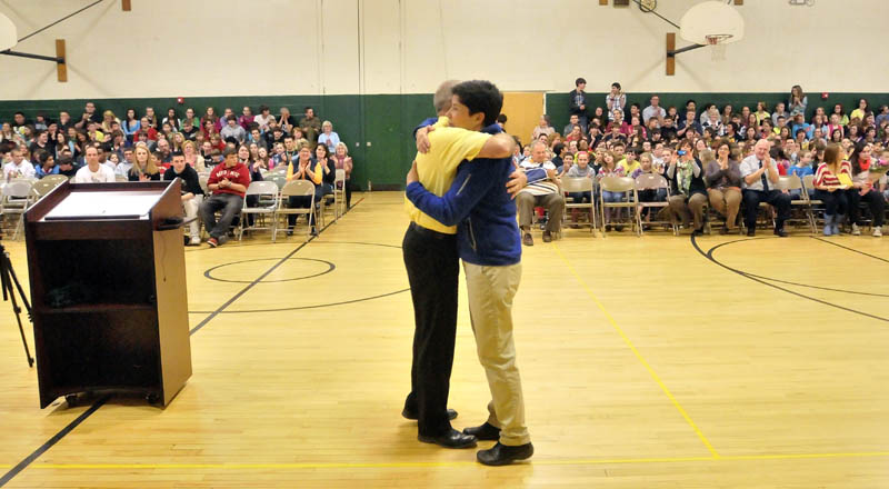 Marisa Weinstein, music teacher at Warsaw Middle School in Pittsfield, receives a hug after she was presented the Maine Music Educators Association Educator of the Year award at the school on Tuesday.