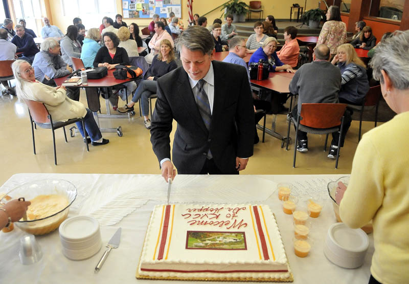 Richard Hopper cuts a cake in his honor, as new president of Kennebec Valley Community College in Fairfield, on Monday.