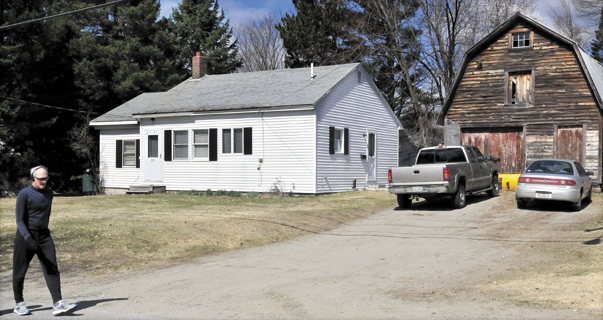 A walker goes past 202 Maple Ave. in Farmington where two people committed suicide Monday, police say.