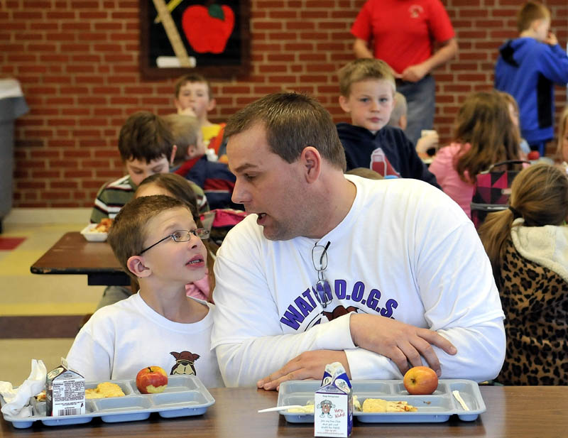 Todd Atwood, a volunteer Watch Dog at Belgrade Central School sits with his son Luke, 8, during lunch on Thursday.