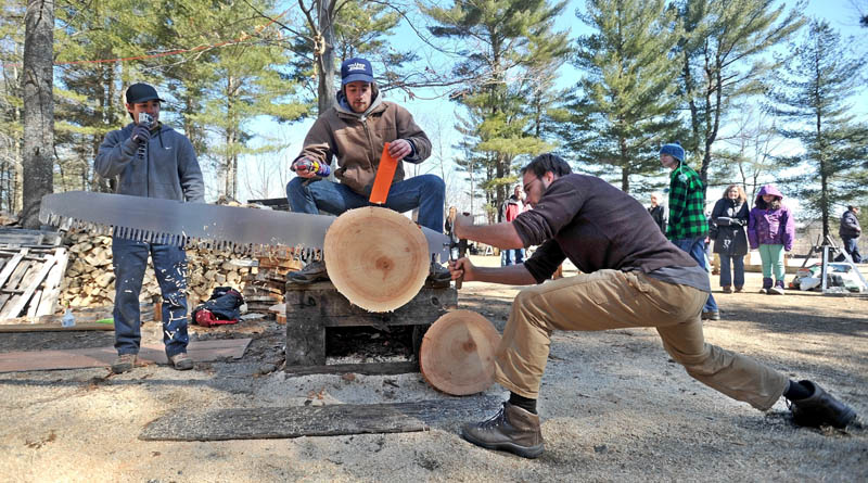Teague Henkle, 21, from the University of Vermont, greases a saw as teammate Eric Donnelly competes in the single-buck comepition at Colby College's annual Muddy Jack & Jill Meet in Waterville on Saturday.