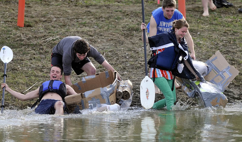 Chris Iacozzi, 18, left, slips as he races into the water as Summer Nay, 20, drags her cardboard kayak in to the water during the first cardboard kayak race at Unity College on Friday.