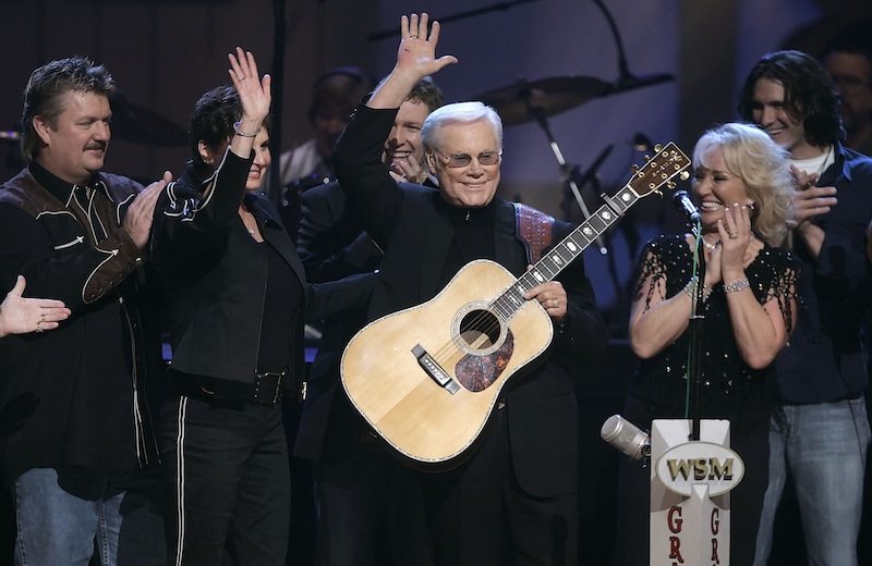 In this Sept. 12, 2006 file photo, Country music legend George Jones waves to the crowd during his 75th birthday celebration at the Grand Ole Opry House in Nashville, Tenn., on Tuesday, Sept. 12, 2006. From left are Joe Diffie; Jones' wife, Nancy; Craig Morgan; Jones; Tanya Tucker; and Joe Nichols. Jones, the peerless, hard-living country singer who recorded dozens of hits about good times and regrets and peaked with the heartbreaking classic
