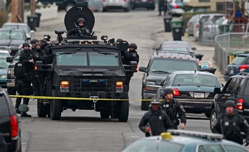 Police in tactical gear arrive on an armored police vehicle as they surround an apartment building while looking for a suspect in the Boston Marathon bombings in Watertown, Mass., on Friday.