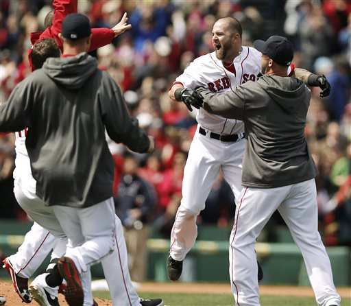 Boston Red Sox's Mike Napoli is mobbed by teammates after his game-winning double scored teammate Dustin Pedroia during the ninth inning of Boston's 3-2 win over the Tampa Bay Rays in a baseball game at Fenway Park in Boston on Monday, April 15, 2013. (AP Photo/Winslow Townson)