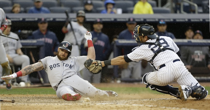 Boston's Jonny Gomes beats the tag of Yankees catcher Francisco Cervelli as he scores on a single by Jacoby Ellsbury in the ninth inning at New York. Gomes had two hits in the Red Sox 8-2 opening-day win on Monday.