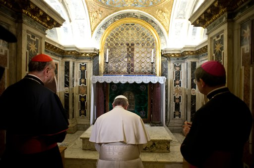 In this picture made available by the Vatican newspaper L'Osservatore Romano, Pope Francis, flanked by Cardinal Angelo Comastri, left, and Bishop Vittorio Lanzani, kneels in front of what is believed to be the burial site of St. Peter.
