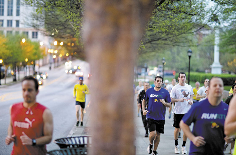 Runners jog along Peachtree Street as part of an organized moment of silence and memorial run to show solidarity with victims of the Boston Marathon bombing, Tuesday, April 16, 2013, in Atlanta. The explosions Monday afternoon killed at least three people and injured at least 100 others. (AP Photo/David Goldman)