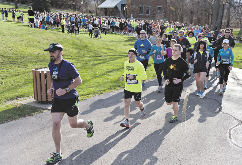 MEANINGFUL STRIDES: Brett Beier, left, leads the Solidarity run he organized Tuesday in Kalamazoo, Mich. to honor the victims of the Boston Marathon bombing. erik;holladay photography;weddi