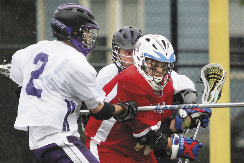GAINING MOMENTUM: Messalonskee's Nate DelGiudice works against two defenders from Deering during a game in 2011. Lacrosse has slowly made its way up from York and Cumberland County into central Maine since the Maine Principals' Association first sponsored the sport in 1998.