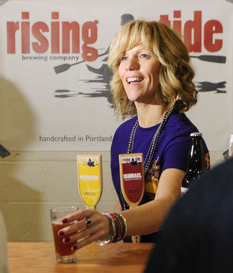 Volunteer pourer Penny Vaillancourt hands a glass of Ishmael American Copper Ale to a customer at the Rising Tide booth on Saturday during the Central Maine Brew Fest at the Augusta armory.