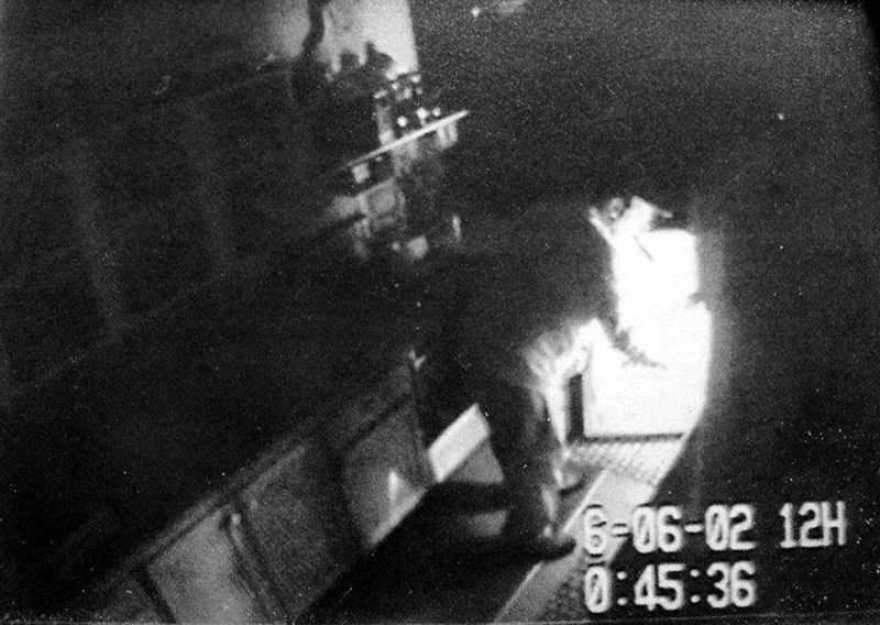 A surveillance photo shows a person, alleged to be Christopher Knight, the North Pond Hermit, burglarizing a structure. Some of the hundreds of those whose camps and homes were allegedly burglarized by Knight feel sympathy for the man, who reportedly survived 27 years in the Rome woods by pilfering food and supplies; others feel violated, and say they're glad he's locked up.