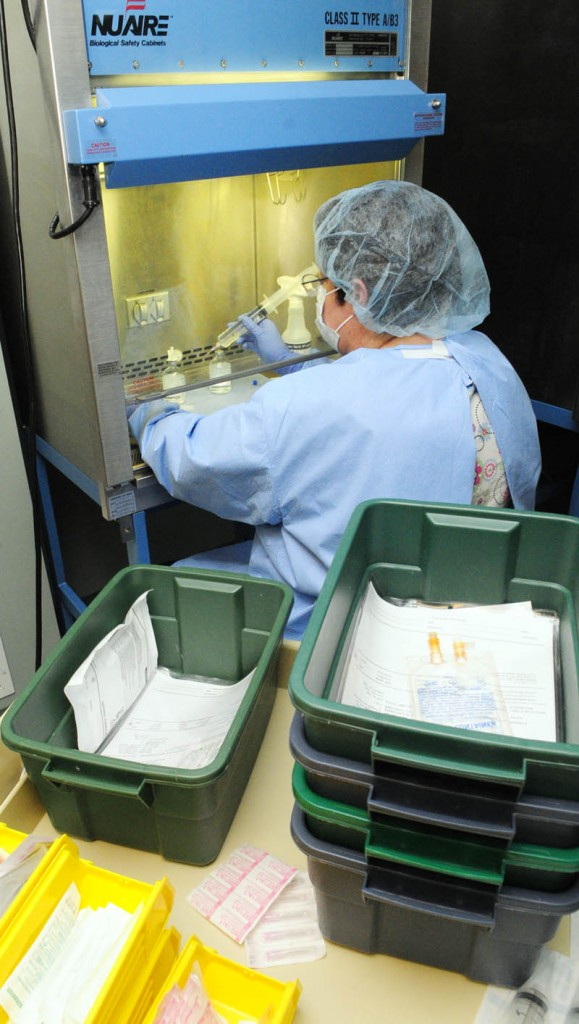 Pharmacy technician Suzanne Goddard works under a hood, preparing intravenous bags of medicines, in the sterile room on April 12, at Kennebec Pharmacy & Home Care in Augusta.
