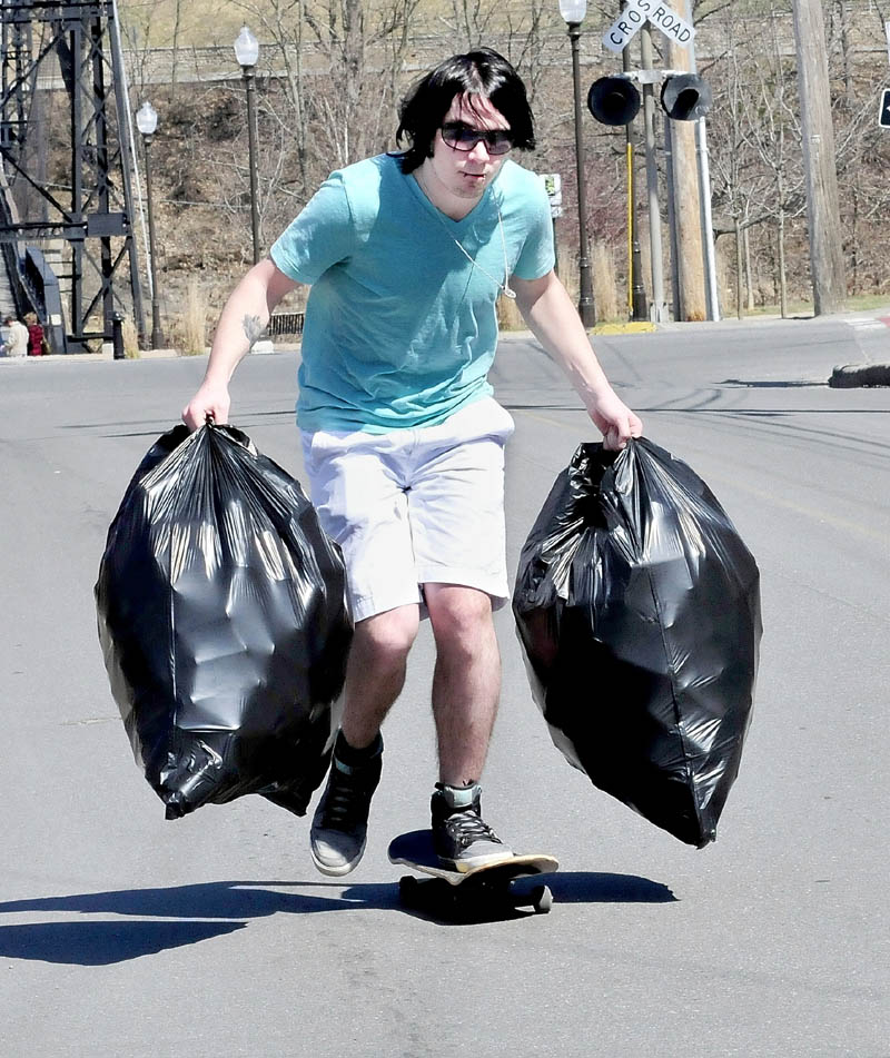 Troy Bowen uses his skateboard to make his way to Jokas redemption center in Waterville to cash in two bags of returnable cans.