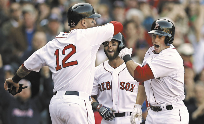 WOOOO: Boston's Daniel Nava, right, is greeted by Dustin Pedroia, center, and Mike Napoli after hitting a three-run home run in the seventh inning of the Red Sox' 3-1 win over the Baltimore Orioles on Monday at Fenway Park in Boston.