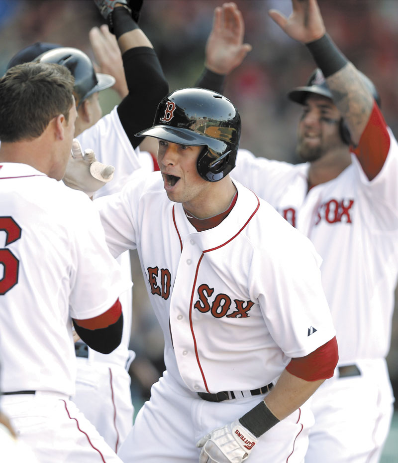 HOME SWEET HOME: Boston's Daniel Nava is greeted by teammates after hitting a three-run home run in the seventh inning of the Red Sox' 3-1 win over the Baltimore Orioles on Monday in Boston.