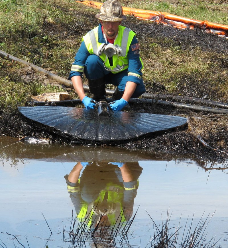 A worker from an oil cleanup crew siphons oil from a drainage channel for Lake Conway in Conway, Ark., on Sunday. There were 364 pipeline spills last year.