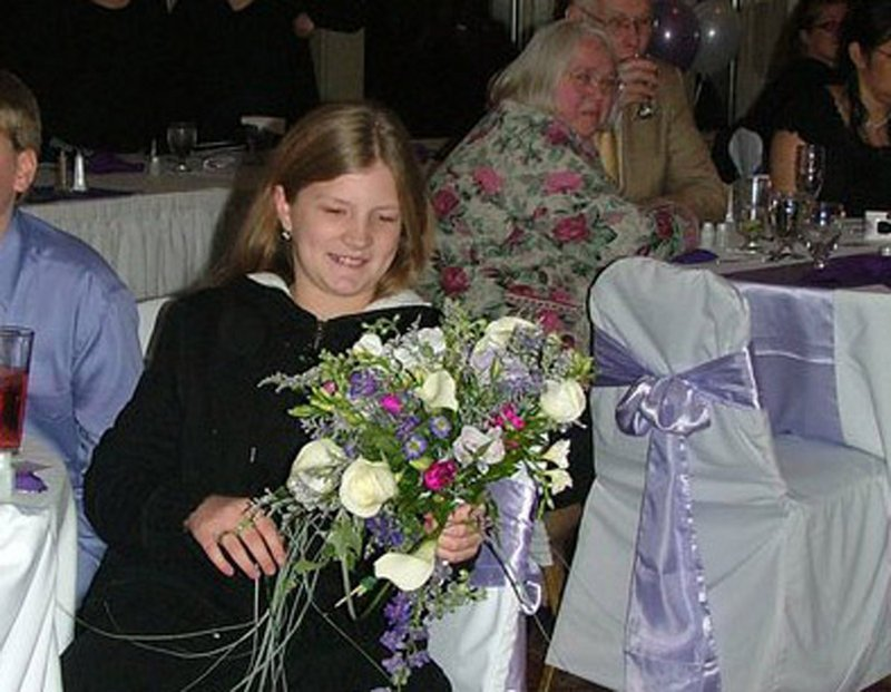Kitty McGuire holds the bouquet she caught at the wedding of Timothy and Hannah McGuire three years ago. She was always the one who caught wedding bouquets, the couple said.