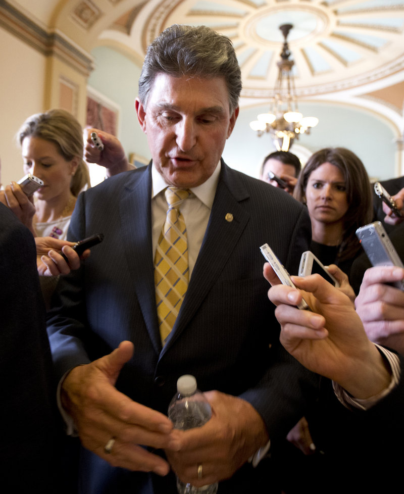 Sen. Joe Manchin, D-W.Va., answers reporters' questions as he leaves the office of Senate Majority Leader Harry Reid, D-Nev., on Capitol Hill in Washington, Tuesday, April 9, 2013, after a meeting on gun control. Reid's determination to stage a vote came despite continued inconclusive talks between Manchin, Sen. Patrick Toomey, R-Pa., aimed at finding compromise on expanding background checks to more gun purchasers. But Manchin left a meeting in Reid's office late Tuesday and said he hoped a deal could be completed on Wednesday. (AP Photo/Manuel Balce Ceneta)