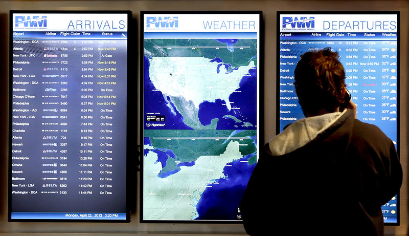 Nick Repenning of Whitefield checks the flight screen to see if a flight is on time at the Portland International Jetport in Portland Monday afternoon on April 22, 2013.