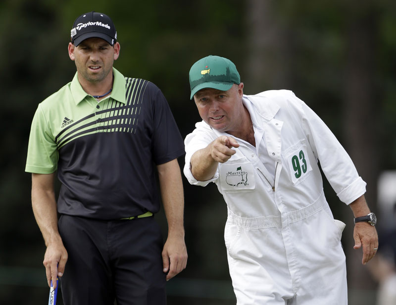 Sergio Garcia, of Spain, listens to his caddie Greg Hearmon on the 14th green during the first round of the Masters golf tournament Thursday, April 11, 2013, in Augusta, Ga. (AP Photo/David Goldman)