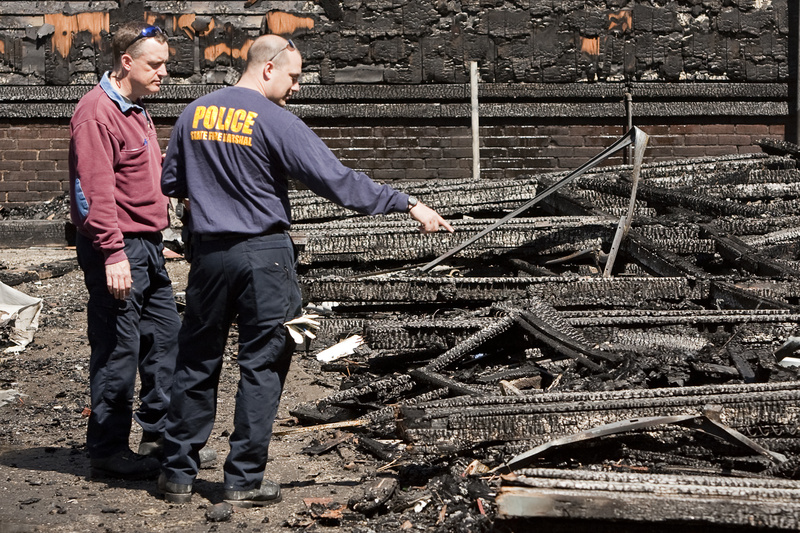 Fire investigators on Saturday morning inspect the rubble at what is believed to be the fire's origin – the garage of a condemned building – for clues about its origin.