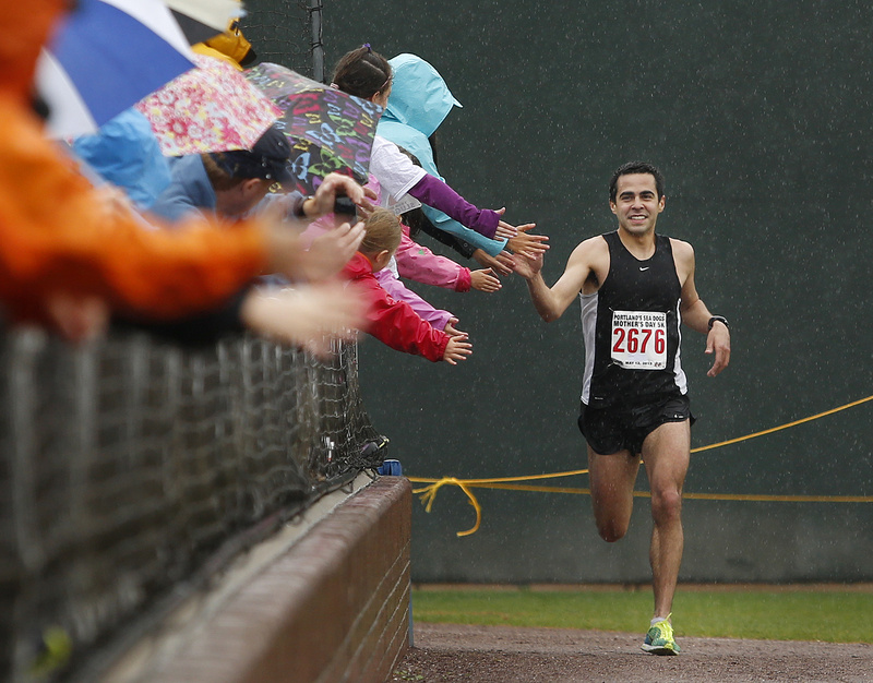 Louie Luchini is all smiles as he rounds the corner toward home plate and the finish line, finishing first in the Portland Sea Dogs Annual Mother's Day 5K road race Sunday.