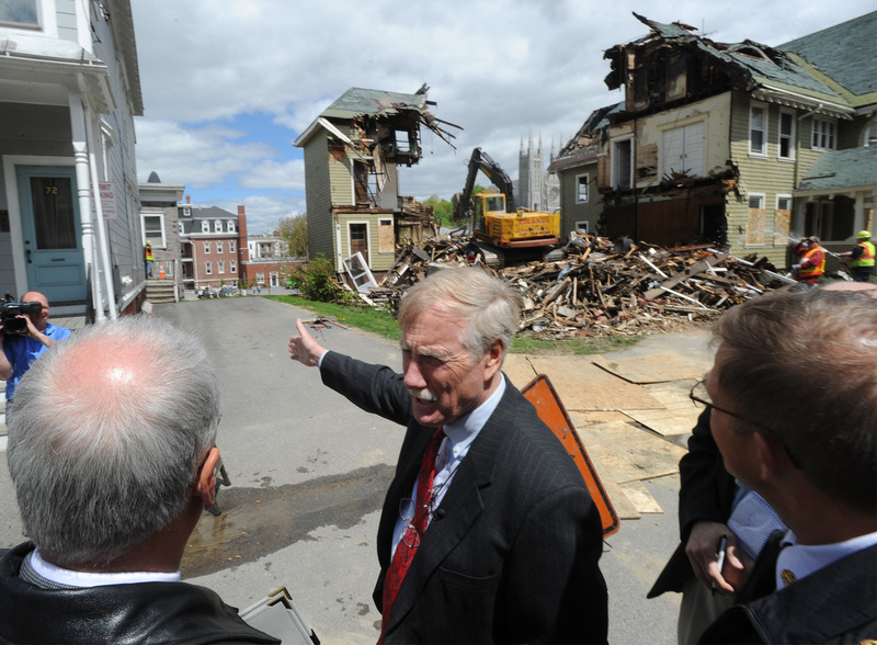 Maine Sen. Angus King tours the fire scenes in Lewiston with city officials Friday, including 80-82 Pine St., where a demolition crew is tearing down the building. King