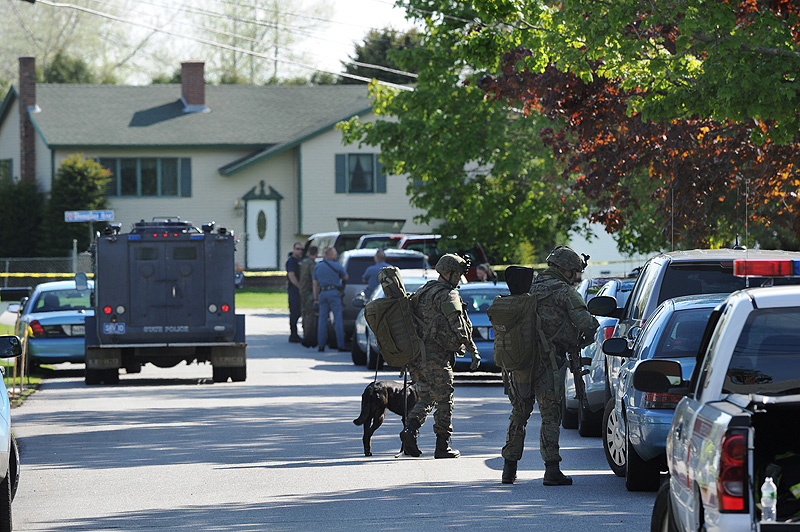 Members of the state police tactical unit join dozens of state and local police on Hillview Avenue in Saco during a standoff with a man in a house on this street beyond the house seen in background.
