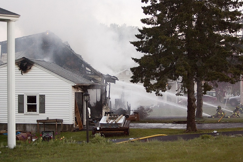 Firefighters put out the blaze set by Saco homeowner Charles Scontras during a standoff with police at his home Saturday. Neighboring homes were doused to keep the fire from spreading.