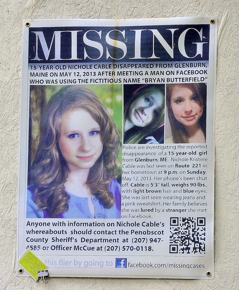 A poster asking for information about the disappearance of Nichole Cable is tacked to a memorial at the corner of her family's driveway and Route 221 in Glenburn on Tuesday, May 21, 2013. Cable's body was found Monday night in a wooded area in Old Town, and a 20-year-old Orono man has been charged with her murder.