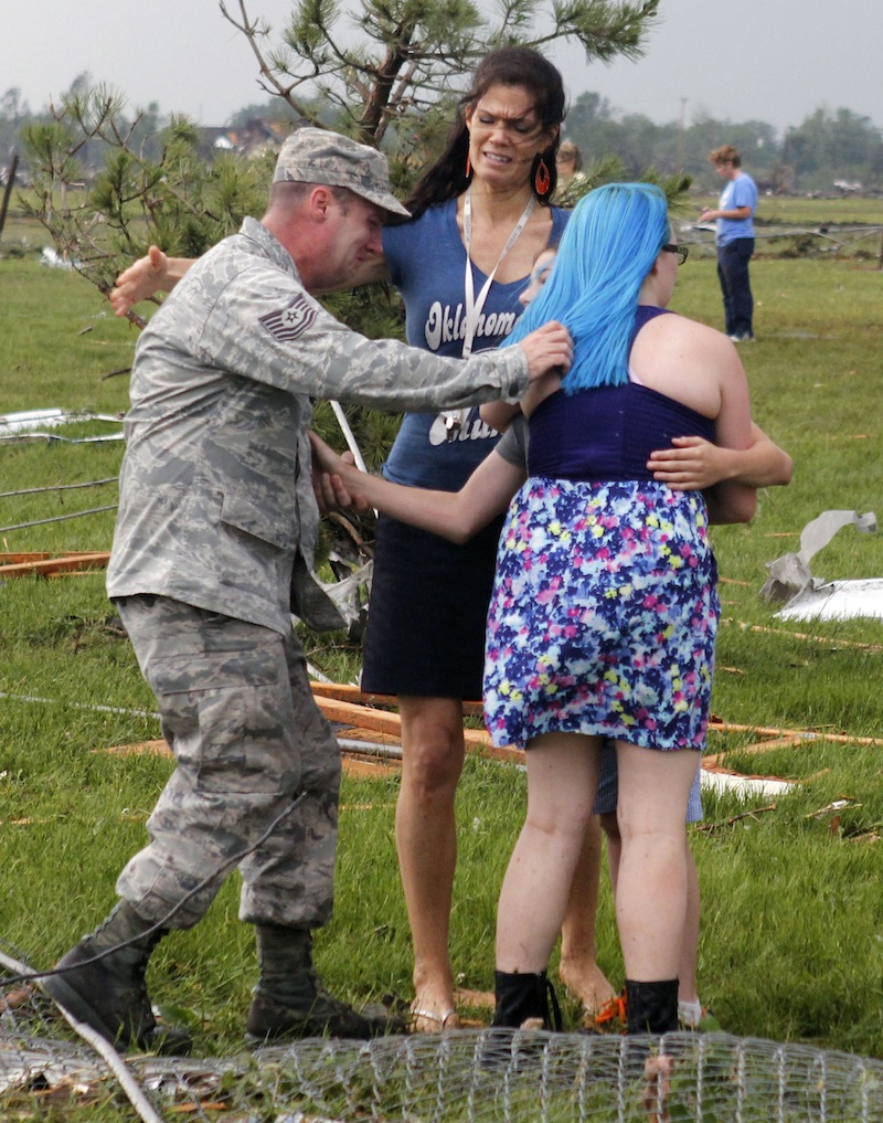 T. Sgt. Robert Raymond, left, runs to embrace his son Ethan, 11, center partially obscured, with his daughter Lily, 17, right, at Briarwood Elementary school after a tornado destroyed the school in south Oklahoma City on Monday, May 20, 2013. (AP Photo/The Oklahoman, Paul Hellstern)