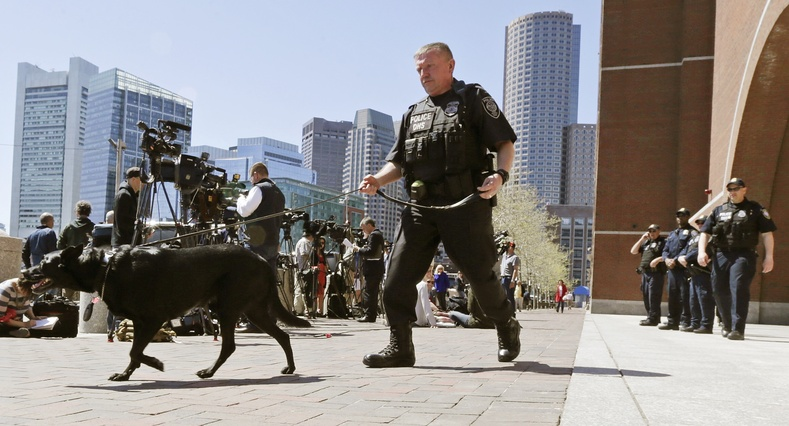 A Department of Homeland Security officer patrols with his dog outside the Moakley Federal Courthouse in Boston, Mass., on Wednesday. Three additional suspects were taken into custody in the Boston Marathon bombing case.