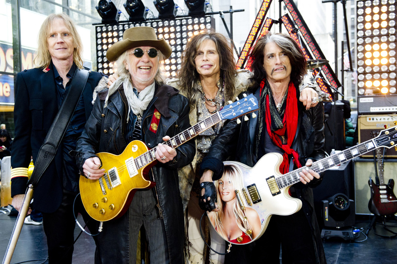 Aerosmith, from left, Tom Hamilton, Brad Whitford, Steven Tyler and Joe Perry, is among the scheduled performers for a Boston Marathon benefit concert May 30 at the TD Garden. Arm Around Shoulder,Concert,Gig,Guitar,Live Performance,On Stage,Small Group of People,Smiling